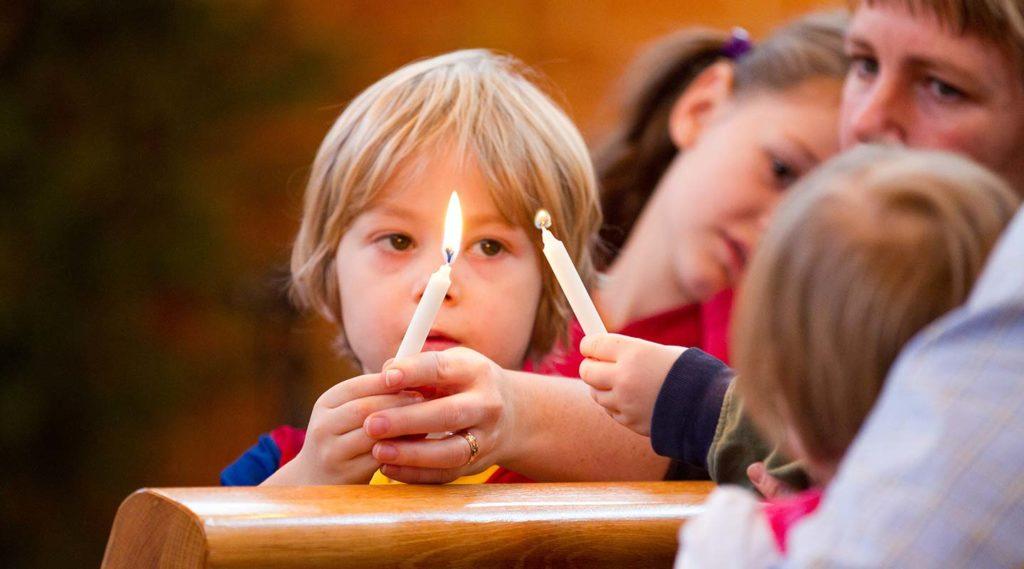 Barn i kyrkbänk med tänt ljus. Foto Jonas Tobin IKON.