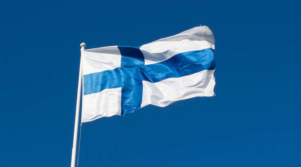 Finsk flagga mot blå himmel. Foto Shutterstock.
