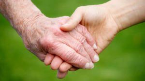 Äldre hand håller ung hand mot grön bakgrund. Foto Shutterstock.