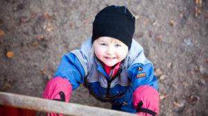 Barn nedanför klätterställning tittar upp i kameran. Foto Josefin Casteryd IKON.