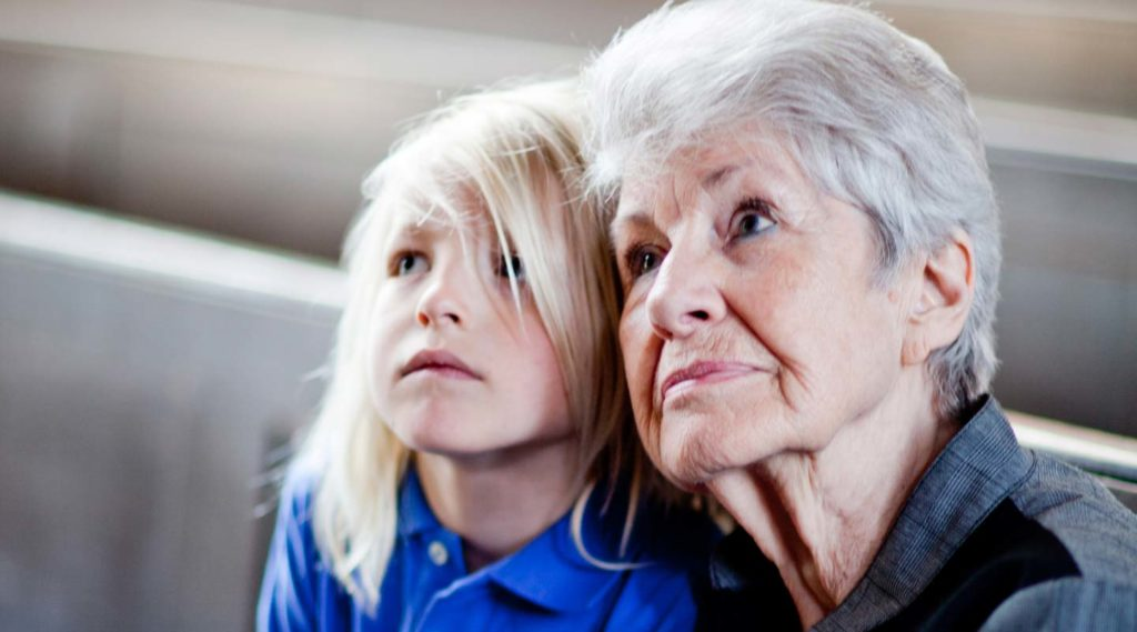Barn och äldre kvinna i kyrkbänk blickar uppåt. Foto Alex & Martin IKON.
