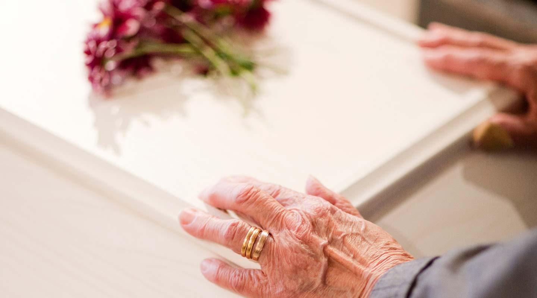 Begravning. Närbild på en äldre persons händer på en ljus kista. Foto Alex & Martin IKON.