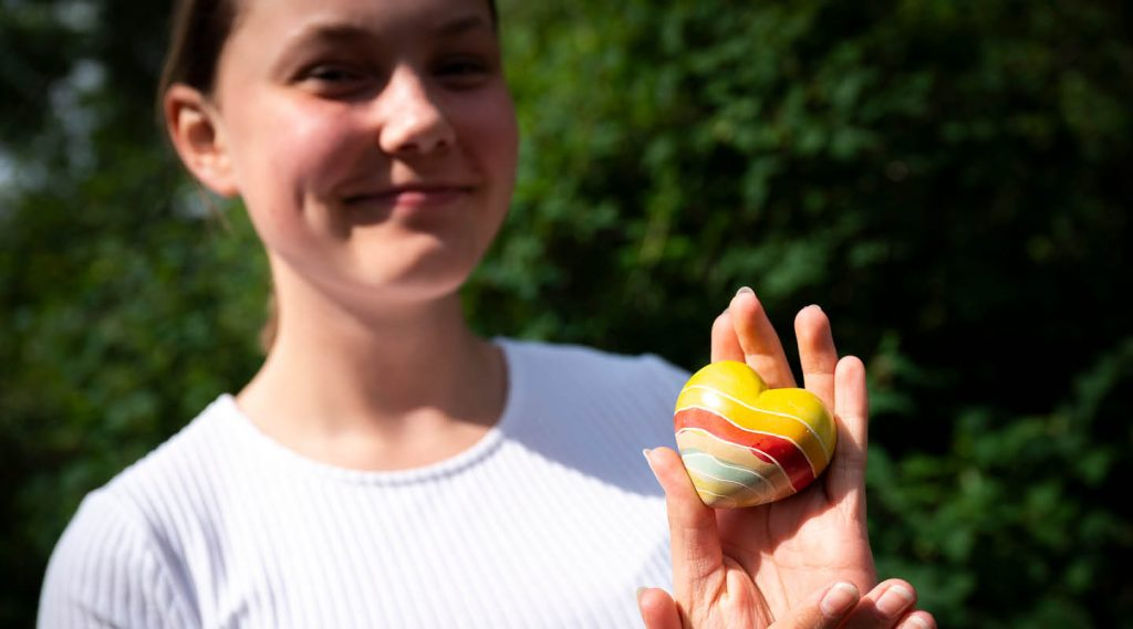 Flicka håller i färgglatt stenhjärta. Foto Magnus Aronson/IKON.