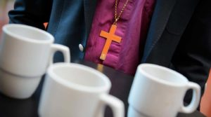 Kaffekoppar ur fokus och präst med kors runt halsen i bakgrunden. Foto Magnus Aronson IKON.