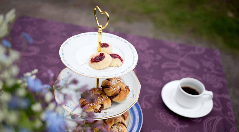 Kaffestuga. Kakor och bullar på fat, en kaffekopp på lila duk. Foto Evelina Carborn 2015.
