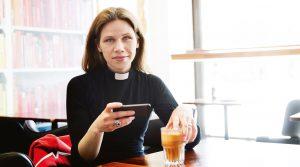 Kvinnlig präst med kaffekopp och mobil tittar in i kameran. Foto Alex & Martin/IKON.