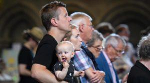 Pappa håller i barn under gudstjänst. Foto Magnus Aronson IKON.
